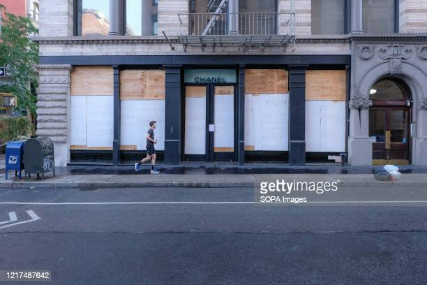 A man jogs by a boarded up Chanel store in SOHO in lowerManhattan on the morning after the eighth day of George Floyd protests in New York City