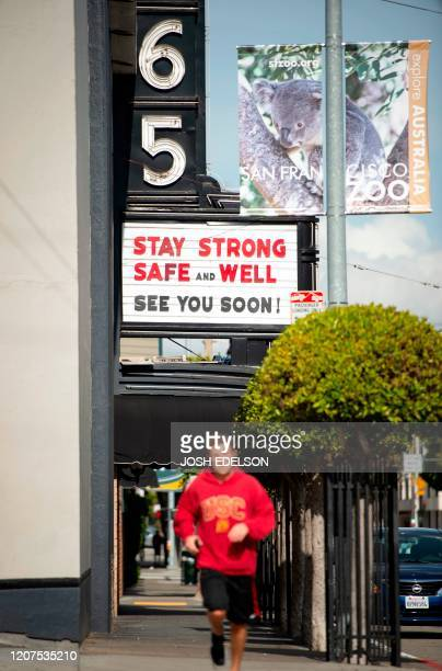 A man jogs by a theatre posting sign of support on it's marquis in a mostly empty San Francisco California on March 17 2020 Millions of San Francisco...