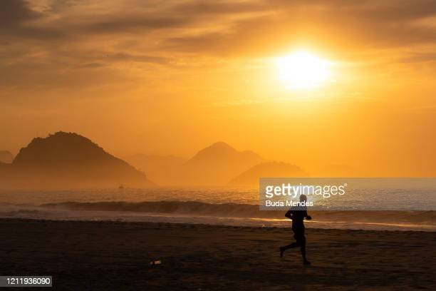 Man jogs by Copacabana beach at sunrise during the quarantine period amid the coronavirus pandemic on May 6, 2020 in Rio de Janeiro, Brazil....