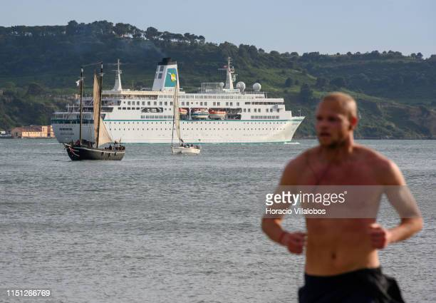 A man jogs by the riverside as MS Deutschland a cruise ship registered in Nassau Bahamas sails on the Tagus River while leaving harbor on her way to...
