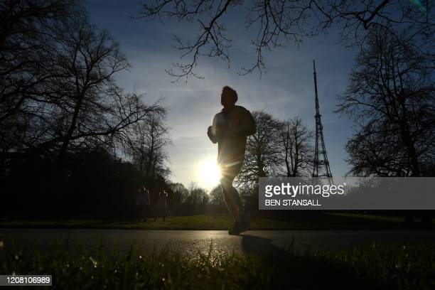 A man jogs in Crystal Palace Park with the wellknown transmitter in the background in south London on March 24 after Britain's government ordered a...