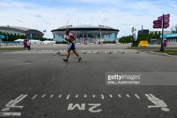 Man jogs in front of of the Saint Petersburg Stadium in Saint Petersburg on June 29, 2021. - The Kremlin conceded that Russia would not reach its 60...