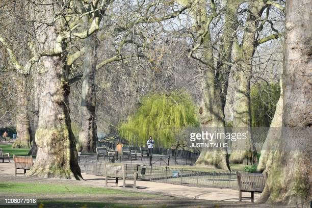 A man jogs in Green Park in central London on March 24 2020 after Britain ordered a lockdown to slow the spread of the novel coronavirus Britain was...