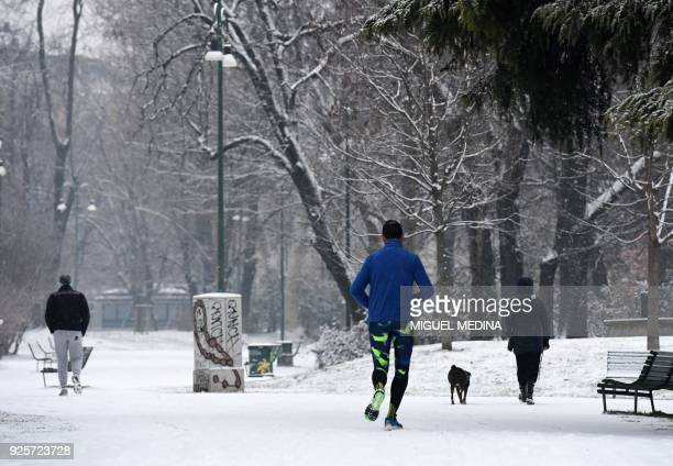 A man jogs in Sempione garden after snowfall in Milan on March 1 2018 Fresh heavy snowfalls and icy blizzards were expected to lash Europe on March 1...