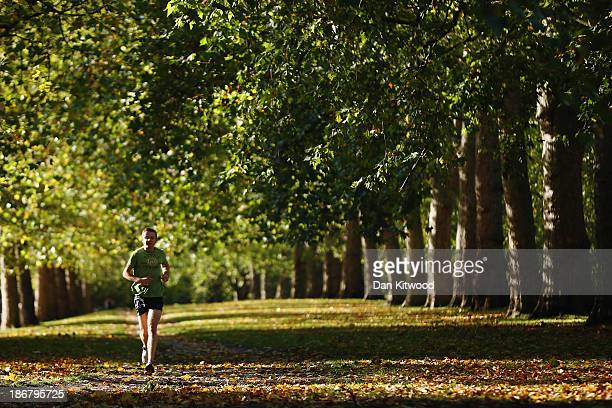 A man jogs in St James's Park on November 4 2013 in London England After the recent stormy weather in many parts of the UK the autumn colours of...