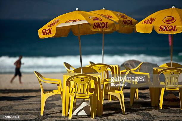 A man jogs on Ipanema beach near tables and umbrellas displaying the logo for Cia de Bebidas das Americass Skol brand beer in Rio de Janeiro Brazil...