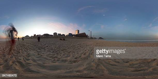 A man jogs on the beach as preparations at the Olympics site for beach volleyball continue on Copacabana beach on July 14 2016 in Rio de Janeiro...