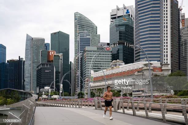 Man jogs on the Esplanade Bridge at the Marina Bay area on the day a 'circuit breaker' takes effect on April 7, 2020 in Singapore. The Singapore...