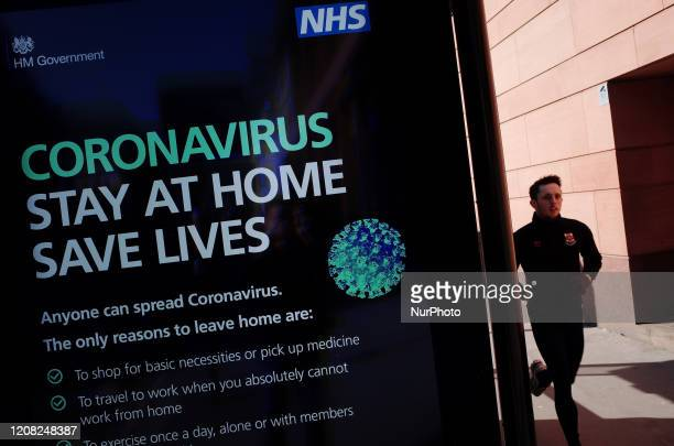 Man jogs past a coronavirus digital information sign asking people to stay at home on a bus stop at Holborn Circus in London, England, on March 25,...
