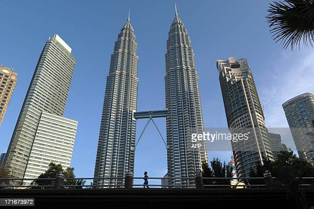 A man jogs past Malaysia's landmark Petronas Twin Towers and commercial buildings as haze clears in Kuala Lumpur on June 28 2013 Malaysia on June 27...