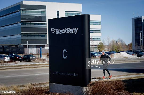 A man jogs past signage displayed at BlackBerry Ltd headquarters in Waterloo Ontario Canada on Thursday March 19 2015 BlackBerry Ltd introduced a...
