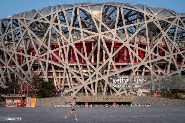 Man jogs past the national 'Birds Nest' stadium, the main site of the 2008 Beijing Olympics in Beijing on March 23, 2020. - World Athletics chief...