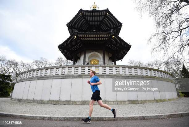 A man jogs past the Peace Pagoda in Battersea Park in London as the UK continues in lockdown to help curb the spread of the coronavirus