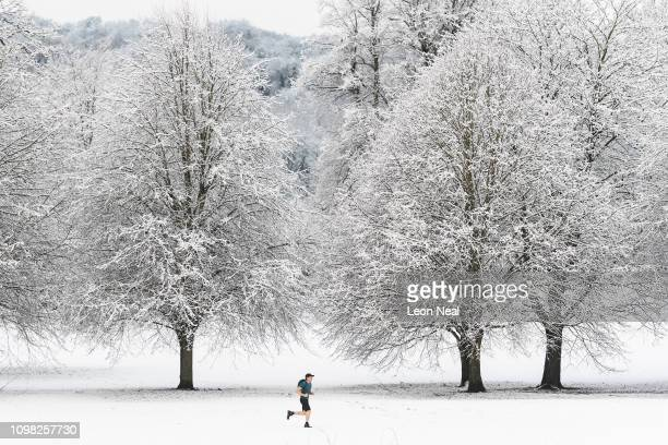 A man jogs through the park as some areas of the United Kingdom see the first snow of the year on January 23 2019 in High Wycombe United Kingdom