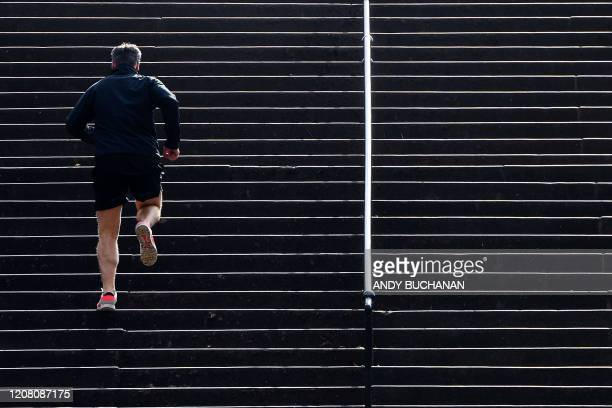 Man jogs to exercise in Queen's Park Glasgow on March 24, 2020 after Britain ordered a lockdown to slow the spread of the novel coronavirus. -...