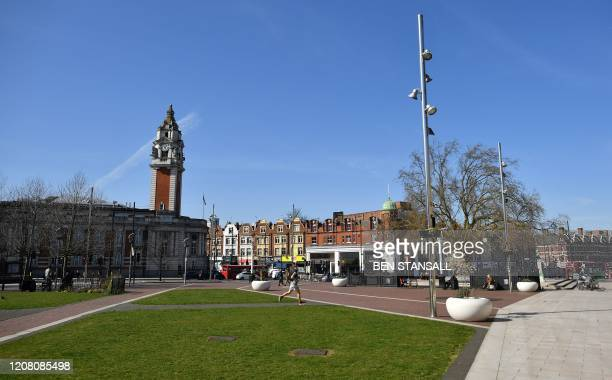A man jogs to exercise through an empty Windrush Square in Brixton south London on March 24 2020 after Britain's government ordered a lockdown to...