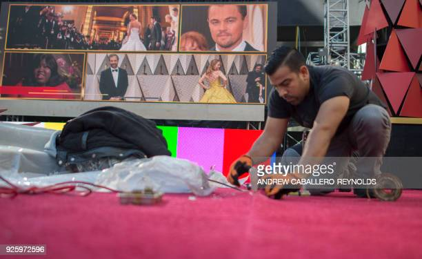 A man joins sections of the red carpet during preparations for the 90th annual Academy Awards week in Hollywood California on March 1 2018 / AFP...