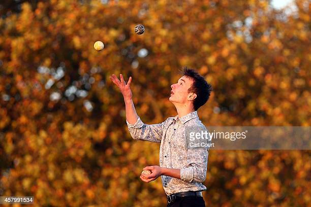 A man juggles in front of an autumnal tree on Primrose Hill on October 28 2014 in London England Warmer than usual weather has seen London...