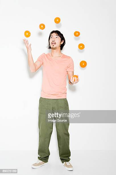 man juggling oranges - juggling stock pictures, royalty-free photos & images