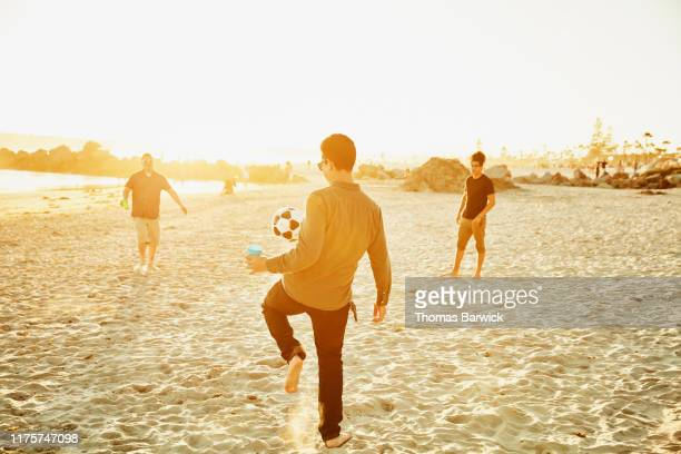 Man juggling soccer ball while playing with friends on beach