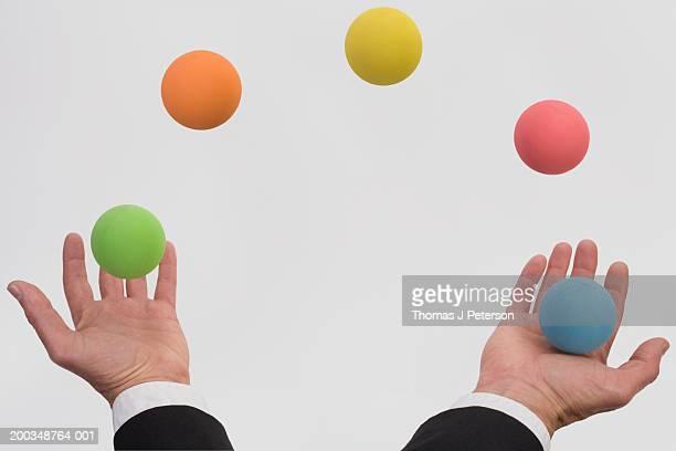 Man juggling various colored balls (Digital Composite)