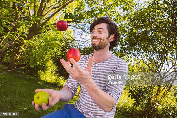 Man juggling with fruit in garden