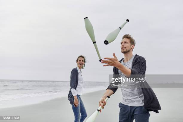 Man juggling with juggling clubs on the beach