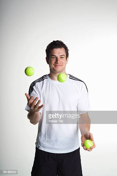 a man juggling with tennis balls - juggling stock pictures, royalty-free photos & images