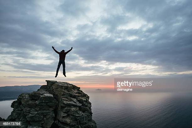 Man jump on top of the cliff