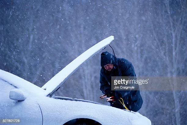 Man Jump Starting Car in Snow