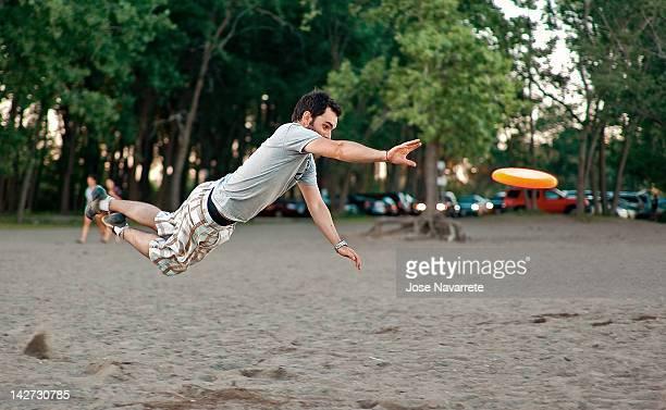 man jumping after frisbee - つかまえる ストックフォトと画像