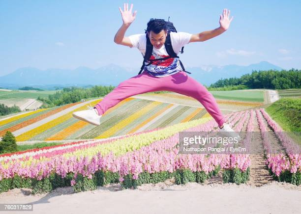 Man Jumping Against Flowerbed With Arms Raised