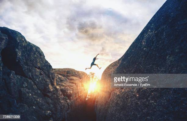 man jumping against sky during sunset - avontuur stockfoto's en -beelden