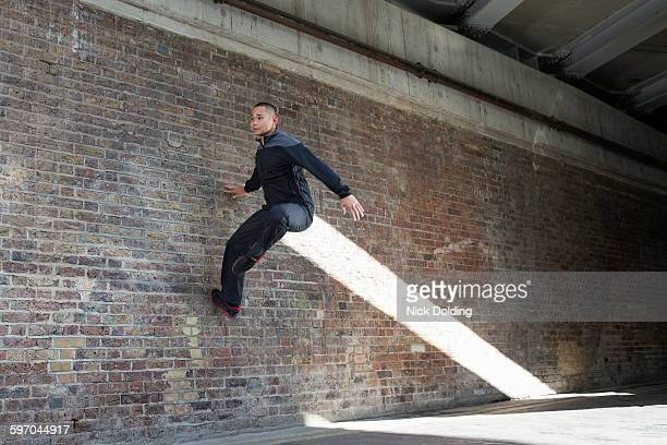 Man jumping against wall in urban setting