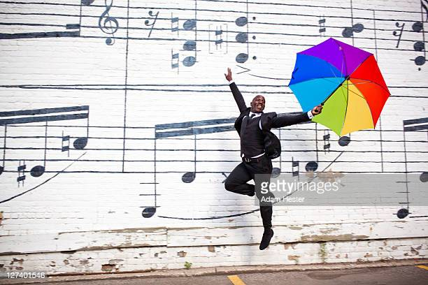 a man jumping and dancing with an umbrella outside - multi colored suit stock photos and pictures