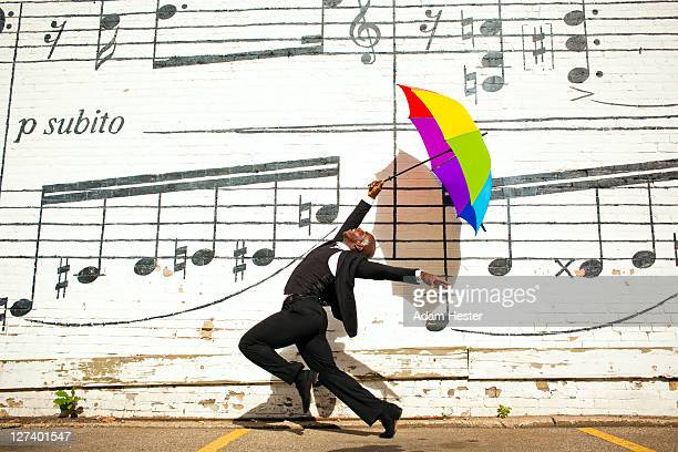 a man jumping and dancing with an umbrella outside - musical note stock photos and pictures