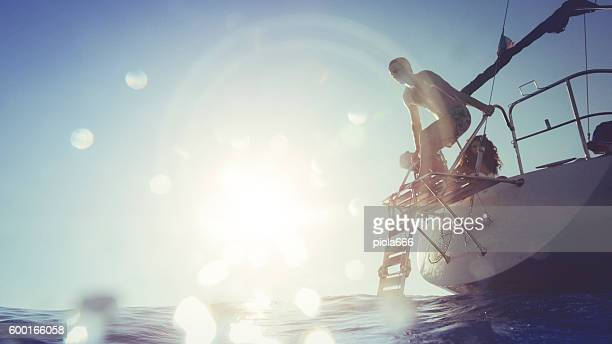 Man jumping and diving from a yacht sailboat