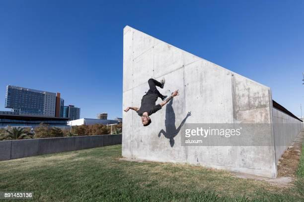 mann, springen und backflips beim üben von parkour in der stadt zu tun - le parkour stock-fotos und bilder