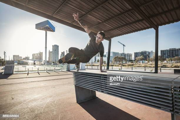 mann springen und üben parkour- in der stadt - le parkour stock-fotos und bilder