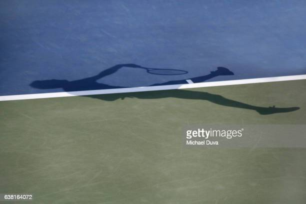 Man jumping and striking tennis ball, playing tennis, noted in her shadow silhouette