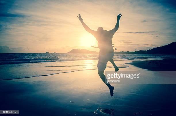 男ジャンプビーチで朝の太陽光線を