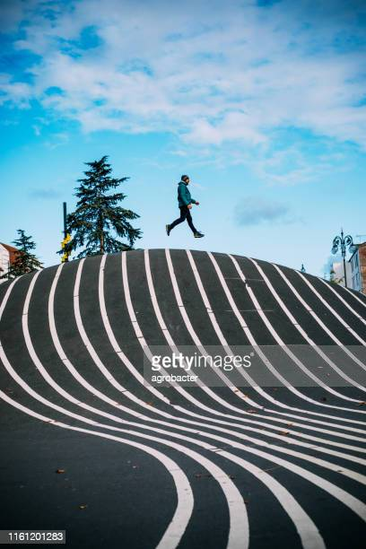 man jumping at superkilen park in copenhagen - copenhagen stock pictures, royalty-free photos & images