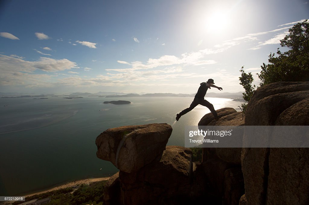 A man jumping between 2 rocks on a mountain top : Stock Photo