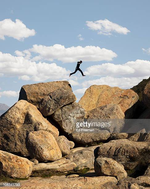 Man Jumping Between Two Boulders