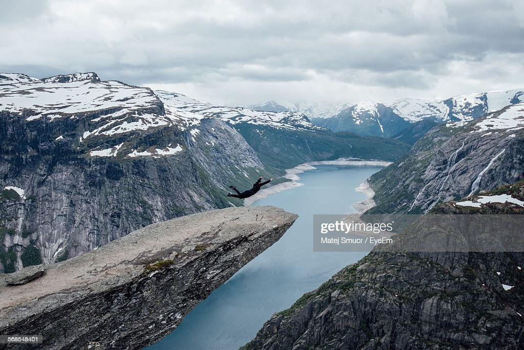 Man Jumping By River Amidst Snow Covered Mountains Against Cloudy Sky : Stock Photo