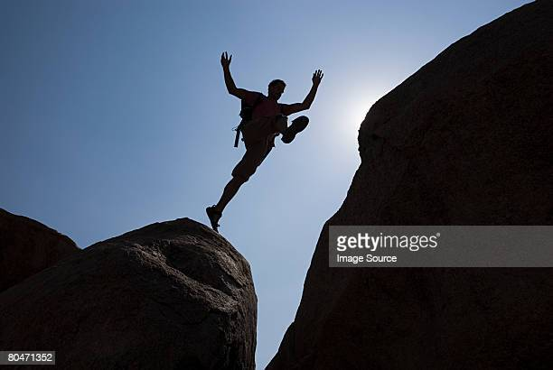 Man jumping chasm