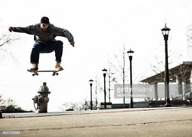 Man jumping fire hydrant on skateboard.