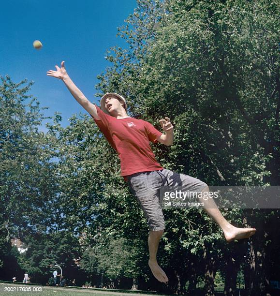 man jumping for ball in park, low angle view - attraper photos et images de collection