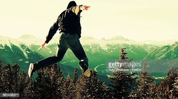 Man Jumping For Joy In Mountains