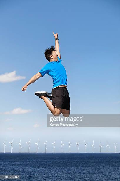 Man jumping for joy over wind turbines